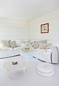 Low coffee table and ottoman next to a coffee table in front of upholstered seating in a white paneled living room