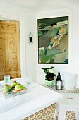 White flowering potted plant and candle lantern below modern painting on white wall next to pale wooden door