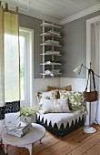 Floor cushion chair with many scatter cushions in corner of small room below narrow bookcase