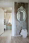 Oval mirror with mirrored frame on rustic wall; flamboyant bed with translucent curtains in background