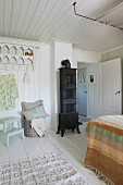 Black stove in white wood-clad room with pretty clothes rack and lavish bed
