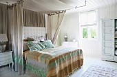 Lavish bed with quilted headboard and airy, embellished curtains in sunny bedroom