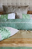 Embellished linen scatter cushions against quilted headboard of bed with striped linen bedspread