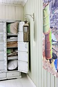 Stacked bed linen and pillows in open, vintage linen cupboard; large lantern on wall next to modern artwork