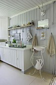 Skandinavische weiße Küchenecke mit nostalgischem filigranem Waschtischmöbel, Waschkrug und Waschschüssel darüber ein Wandspiegel