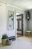 Hallway of Scandinavian wooden house with window casement upcycled as pinboard and open, painted interior door