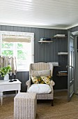 Comfortable wicker reading chair and stool in front of sunny window and wood-panelled wall with small bookshelves