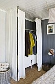 Wardrobe created from clothes rail above white sideboard and screened by curtains in corner of room