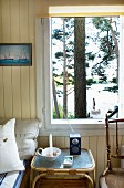 Bright, wood-clad room with tranquil view of lake through tall pines