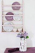 Pastel pink plate rack on white wall above shabby chic vase of fragrant lilac on table