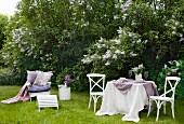 Idyllischer Garten mit blühendem Flieder; im Vordergrund ein gedeckter Tisch und ein Gartenstuhl mit bequemen Kissen