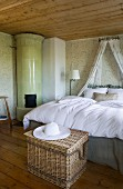 Lavish bed with canopy in pleasant room with many wooden elements, green patterned wallpaper and round tiled stove in corner