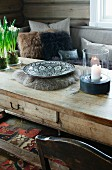 Candle lantern and ethnic bowl on rustic wooden coffee table in front of sofa with fur scatter cushions