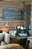 Framed photos and retro table lamp on rustic table against wooden wall with collection of pewter plates in wall-mounted plate rack