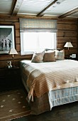 Double bed with bedspread and scatter cushions below window in rustic bedroom in wooden house