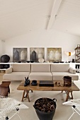 Rustic coffee table in front a designer couch upholstered in light fabric in a modern living room and a row of pictures on the wall
