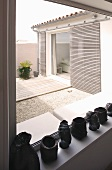 Heads and containers made of black material on a window ledge and a view of a courtyard with sliding architectural elements on the home's facade