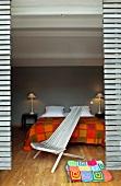 Blick durch Öffnung auf Bett mit karierter Tagesdecke in verschiedenen Rot- und Gelbtönen