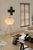 Living room with floor lamp and paper lamp shade behind a designer, wooden stool