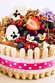 A white chocolate cake with fresh berries and pansies