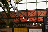 Delicate metal frame of hall roof structure with string of lights