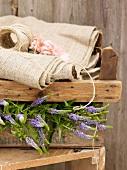 Wooden crate of garden flowers under folded hessian