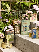 Steps decorated at side with flowers in vintage tin cans used as vases
