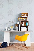 Old wooden crates used as shelves on desk and Charles Eames rocking chair