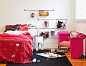 Girl's bedroom with red bed linen with heart motif; pink bins and wire baskets on wall for storing toys