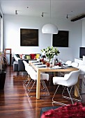 Festively set dining table, white shell chairs and two dark paintings in open-plan loft interior