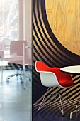 Contemporary office with Eames chair in front of a plywood wall painted with circular shapes (Red Bull Central, Amsterdam)