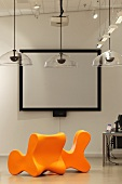 Vibrant orange chairs and transparent hanging lamps in front of a screen with a black frame (Bibliothek Hoofddorp-Centrale)