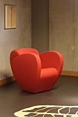 Modern orange armchair in front of a raw concrete wall with patterned floor (Floriande Public Library)
