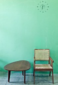Kidney-shaped table and wooden chair from the 50s in front of a mint green wall with simple relief wall clock (Mill Owner's Association Building)