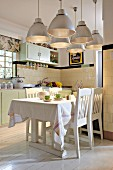 Large, retro-style pendant lamps with metal lampshades above dining area in open-plan country-house kitchen