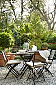 Classic garden table and chairs on gravel floor; groups of shrubs, trees and box bushes in terracotta pots in background
