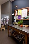 Küchentisch mit Edelstahlplatte vor schwarz getönter Wand