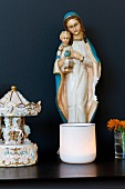 Madonna figurine and tea light holder on dark shelf against black wall