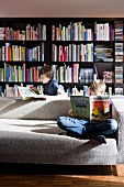 Children reading on comfortable designer couch in front of large bookcase