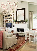 Interior with traditional-style sofa set in front of fireplace & white-painted dining set