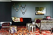 Stags' antlers and naïve artwork above eclectic seating in wild mixture of styles - antique sofa with zebra patterned upholstery combined with Oriental side tables and pouffes