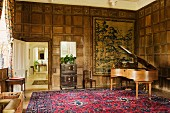 Grand piano with natural wood finish in room with coffered wooden walls and view into hallway through open door