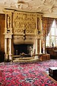 Patterned rug in front of grandiose fireplace with carved stone garlands and sculptures in grand salon