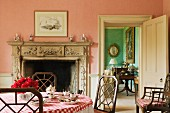 Pink breakfast room with rustic tablecloth on table in front of open fireplace with stone mantelpiece and view of adjoining room through open door