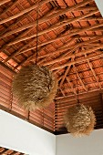 Textured pendant shades hang from beamed ceiling of beach house retreat in the Indian state of Goa