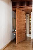 Trennwand aus Massivholz; dahinter ein hölzerner Waschtisch und ein Wandspiegel