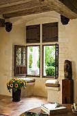 Window aperture in Mediterranean country house - vase of sunflowers on floor below open window with view of garden