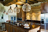 Finnish, designer pendant lamps made from wooden slats above free-standing kitchen counter and cupboards with solid wooden doors in rustic interior