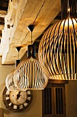 Finnish, designer pendant lamps made from wooden slats hanging from wood-beamed ceiling