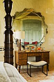Dressing table and stool below round mirror with ornate frame and partially visible bed with wooden post